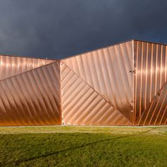 Each facet of this crystalline museum in Poland by OVO Grabczewscy Architekci is covered in a sheet of corrugated copper to resemble the flames of a fire.