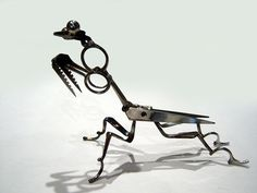 This Praying Mantis is made from TSA-confiscated scissors. The face is made from part of a TSA-confiscated multi tool. The eyes are large ball bearings.