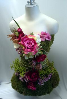 Mannequin dressed in festive silk flowers and moss.