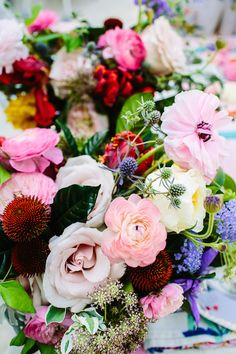 Roses, gardenia foliage, and dusty miller are accented by ranunculus, parrot tulips, scabies, & clematis.