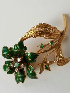 Floral polychroom broche in goud groen glazuur en edelstenen.  Floral broche met uitstekende polychrome decoratie gemaakt van 18 kt goud edelstenen en glazuur. Art decostijl.Beschrijving:Belangrijkste bloem met 6 groene emaille bloemblaadjes met de kroon van bloemblaadjes bekroond door een centrale emerald 25 mm en 5 briljant geslepen diamanten ten bedrage van 010 ct (elke 002 ct).Hieronder is het een bloemetje en een tak met drie diamanten meten van elke 15 mm.De broche is ontworpen met…