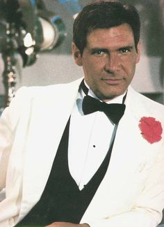 Indiana Jones in a white dinner jacket, black brotie, black vest, and red bout