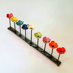 A truly original candelabra comprising of nine different colored ceramic flowers, the slightly higher central white flower serving as the Shamash. This ceramic Menorah is very unique and special. It will look great in your window during Hanukkah time and will add a sense of style to your home all year long. The colors are so fun, it will surely delight everyone in the family! The ceramic flowers are made of white clay and glazed in the following colors: Wine Yellow Turquoise Blue White…