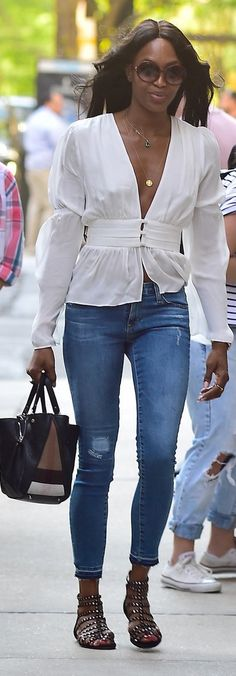 Naomi Campbell looked carefree in a breezy blouse with a plunging neckline. She completed her effortless outfit with embellished sandals, cropped denim, layered necklaces, oversize sunglasses, and a colorblock bag.