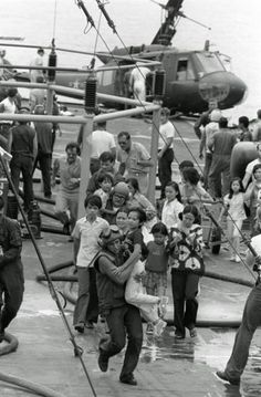 U.S. Marine helicopter crewmen carry Vietnamese civilians to safety aboard the USS Blue Ridge, after their evacuation helicopter crashed on the deck of the amphibious command ship.
