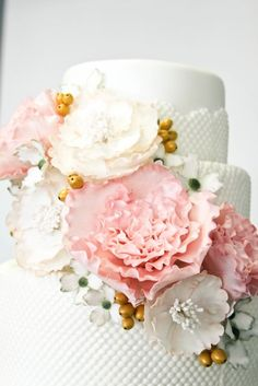 Detailed shot of the pretty wedding cake with exquisite flowers and a textured fondant layer from www.sweetandsaucyshop.com from long beach, california