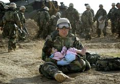 U.S. Navy Hospital Corpsman HM1 Richard Barnett, assigned to the 1st Marine Division, holds a child after she was separated from her family during a firefight [2003]