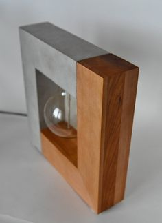 This lamp is part of our Concrete and Wood collection. The 50 50 split between materials along with pure and straight lines infuse this lamp a unique touch of simplicity and class. This piece of art design is handmade in our home workshop located in Wood Slab Table, Table Lamp Wood, Wood Lamps, Rustic Lamps, Desk Lamp, Concrete Crafts, Concrete Lamp, Concrete Design, Tiffany Table Lamps