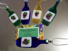 a wine bottle ornament/sun-catcher. Hand-cut and kiln-fused in our studio. Hang in your window or on your tree via satin ribbon tied to securely attached (epoxy) bail. Measures approx. 1.25 inches wide by 3.75 inches tall, not including ribbon. LIsting is for one ornament. for 15.00