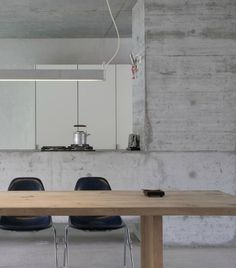 12 Concrete Interiors: The rough finish of the concrete island and oversize column are balanced by the smooth wood table with contemporary lines, and modern black chairs. The stainless/wood teapot adds a slightly Japanese flavor.