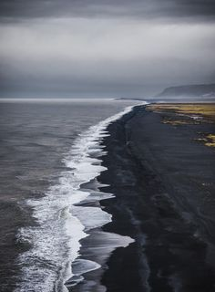 Black volcanic sand shore as far as the eye can see - Dyrhólaey, Iceland