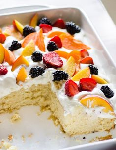 Easy Summer Cake with Fruit and Cream. One-bowl butter cake baked in a pretty dish, topped with whipped cream and piles of summer fruit.