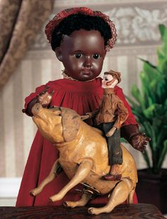 """*FRENCH BROWN-COMPLEXIONED BISQUE CHILD DOLL FOR G.A. SCHWARZ, `6"""" Bisaque socket head w rich brown complexion, brown glass inset eyes, black painted lashes + brows, accented nostrils + eye corners, open mouth, four teeth, black fleecy wig, brown composition + wood ball-jointed body, antique costume.  Marks: 50 2 Made in Germany. COMMENTS: C. 1890"""