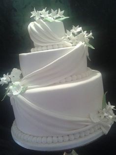 3 tier wedding cake with draping and delicate stephanotis and hydrangea.
