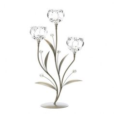 Candlelight blooms with crystalline beauty, thanks to this trio of gorgeous blooms. The iron base features stylized leaves and crystalline flower buds. Add the candles of your choice. Candles not included. Weight 2.4 pounds Dimensions 10 x 5.5 x 18.5 Iron and glass.