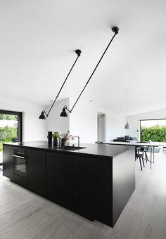 Køkkenet fra Kvik består af højskabe i hvidt og køkkenø i sort. Bordpladen er i sort granit med armaturer fra Vola.