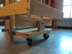 Mobile multi-tool workstation wheel mechanism.  Lifting the table and pulling the string swings the stop block up allowing the table to be lowered on its legs.  Notice that the legs also serve as the axle supports.