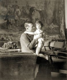 """Adolf Hitler and Uschi (Ursula) Schneider, daughter of Herta Schneider, a close friend of Eva Braun from childhood, pose in Hitler's study at the Oberslazberg, 1942. Hitler was strongly fond of children although, privately, he would admit that he could never be a father because he was devoted """"body and spirit"""" to """"serving"""" the German people."""