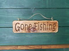 Gone Fishing sign for the fisherman in your life.  Great for cabin, beach, or lake house decor.Measures  approx. 3.5 inches tall and 13 inches wide.Can hang on the wall, a tree limb, or a pole with the attached twine.  We have one ready to ship.Wood is a natural product and the grains and knots in it are all part of its beauty.