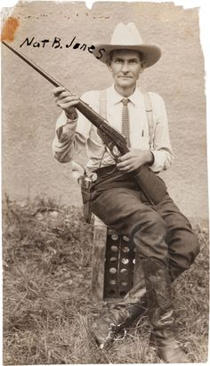 "[Texas Rangers]. Nat B. Jones Photograph, circa 1920. Measuring 3.25"" x 5.75"", Nat Jones, who went by the nickname ""Kiowa,"" sits on a box crate holding a lever action, .30 Army Winchester Model 1895, the ubiquitous Colt revolver (with ivory handles) holstered on his right hip."