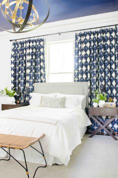 Bed in front of windows. Make a small window feel large with curtains hung wider than the window frame.