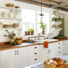 Country Kitchen w/white open shelves, white cabinets, counter-to-ceiling beadboard backsplash.  i love the exposed, whitewashed ceiling beams&the white enamel cast iron sink.