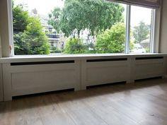 Groot raam, radiatorbekleding, brede vensterbank.