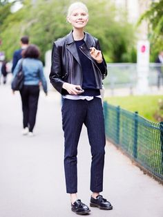 A white t-shirt, black sweater, leather motorcycle jacket, and pinstripe cropped pants are paired with Doc Martens loafers