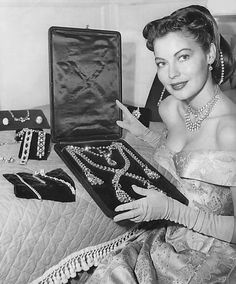 """Ava Gardner looks at fake jewelry created by the MGM prop department for use in """"The Great Sinner"""". November, 1948"""