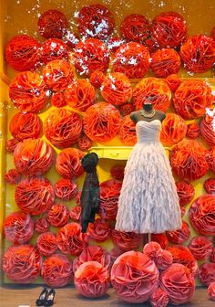 Paris window display  Tissue bulbs, wedding season: Although lovely, the background an supporting elements should not overwhelm the subject and make it appear small and less interesting... Color choices and placement could have been revised here to increase attention to dress!