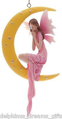 Lovely little wish fairy hanging decoration the fairly is dressed in a pretty pink dress she is kneeling inside a crescent moon that is decorated