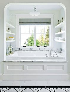 This arched alcove built-in tub is tucked under a window with shelves for…