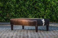 A beautiful cowhide ottoman featuring antique copper studs. This could be in a traditional or modern home.