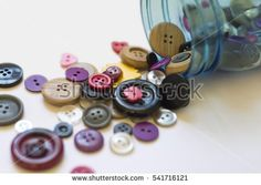 Spilled Jar of Colorful Buttons against a Creamy White Background