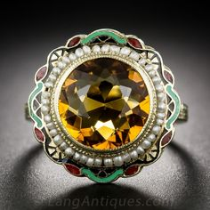 Vintage Golden Citrine and Enamel Ring, This delightful 1930s vintage Art Deco jewel glistens and glows with a round faceted honey colored citrine. The entrancing gemstone is encircled by a tiny seed pearl necklace which, in turn, is framed by a striking design rendered in bright red, green and black enamel. As a finishing touch, the upper ring shank is hand engraved with classic acanthus leaf motifs. 14K yellow gold.