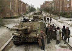A Column of Soviet ISU-122 (Samokhodnaya Ustanovka 122) self-propelled guns during a brief lull in the fighting in a suburb of Berlin, May 1945.  Photographer - Roman Lazarevich Karmen (Рома́н Ла́заревич Карме́н)