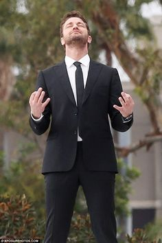 Playful: Gerard, who has previously fronted campaigns for Hugo Boss, adopted a series of poses during the photo shoot, including this Buddha-like hand position that came off as meditative