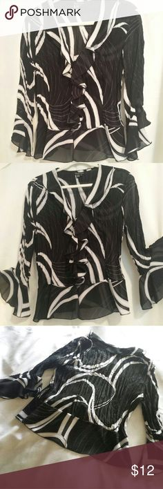 Black and white fancy blouse. Fun, flouncy, and feminine.  Semi sheer with buttons down the front.  Sleeves flare at elbows. Wear over a dress, add a cami and wear with a skirt or pants. Best of all, it's easy to wash. Tops Blouses