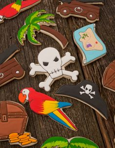 Pirate cookies~                  By cookie decorating, red parrot, Brown treasure chest, blue treasure map, black pirate hat, green Palm tree, white skull and crossbones