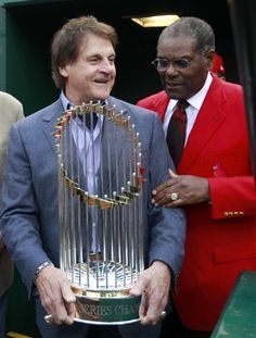La Russa and Bob Gibson hold the 2011 World Series trophy.