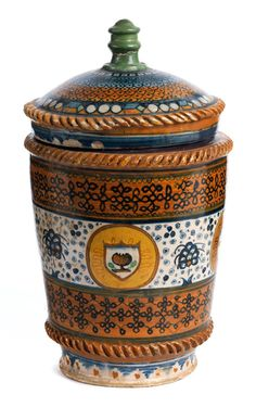 Faenza, XV sec. Auf leicht schmalerem Fuß ein zylindrisches, sich leicht nach oben weitendes Gefäß, hoher Auflagering. Der Deckel flach gewölbt mit Knauf. An den Kanten ...