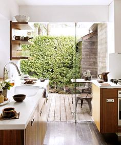 Kitchen with wood floors, wood cabinets, wood shelves, white countertops, white walls, and a large glass door leading to a patio