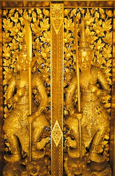 Gold colored figures with swords adorn a temple door in Malaysia