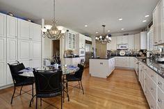 cuisine ouverte sur la salle à manger, une table ronde et des chaises noires, cabinets blancs