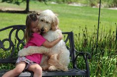 PIC FROM CATERS NEWS. Pictured - Meghan and lilyBelle share a hug - A little girl with a nut allergy has been given a new lease of life thanks to her best friend - a dog that has been trained to sniff out peanuts. Meghan Weingarth, 7, comes out in hives and could go into anaphylactic shock if she eats anything that contains peanuts or almonds. But Meghans faithful companion, LilyBelle has been specially trained to sniff out nuts in her food and keep her out of harms way.