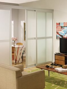 Triple sliding glass room dividers used to create a game room. Installed with frosted glass, a custom frame design, and silver frame finish.