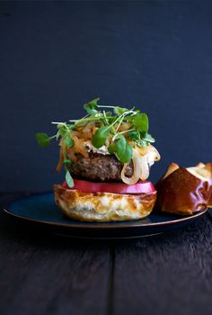 Burger with microgreens, sauteed onions, heirloom tomato, and fresh goat cheese