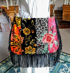 Beautiful vintage cut velvet floral tapestries come together in this boho bag. Pretty pink floral applique with long fringe. Crossbody bag with long handle with brass rings. Inside floral lining with a magnetic snap closure and a zipper pocket. Contrasting back with big floral pocket. Measures 16 X 11 plus 6
