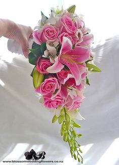 Bride's Cascading bouquet with pink lilies, pink roses, white orchids and foliage, bound in white satin and pinned with pearls    Visit us here:  www.blossomweddingflowers.co.nz  Friend us here:  www.facebook.com/pages/Auckland/Blossom-Wedding-Flowers/2.. I love flowers  Please check out my website www.photopix.co.nz