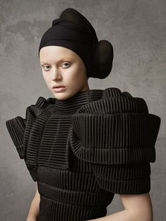 bold black dress with textured fabric detail and layered symmetrical structure with 3D sleeves; sculptural fashion